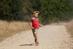 Boy running on dusty road. Seven year old kid running on a dusty road in the countryside Stock Photography