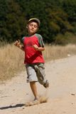 Boy running on dusty road Stock Images
