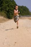 Boy running on dusty road Stock Photography