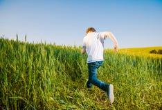 Boy running through field Royalty Free Stock Image