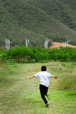 Boy running in field and wind turbines in backgroun Stock Photography