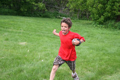 Boy running with a football. A young boy is playing touch football Royalty Free Stock Photos