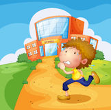 A boy running in front of the school Royalty Free Stock Photography