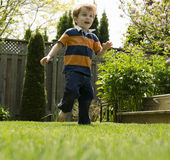 Boy running through grass Stock Photo