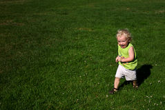 Boy Running on Grass in Park. Two year old boy running on lush grass in park; excited expression; Nikon D200 Stock Photography