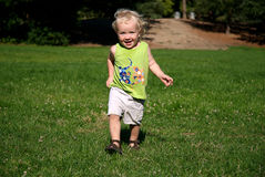 Boy Running on Grass in Park. Two year old boy running on lush grass in park; excited expression; Nikon D200 Royalty Free Stock Photo