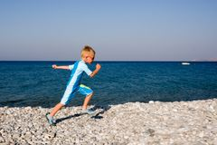 Boy running on gravel beach Stock Image