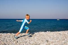 Boy running on gravel beach stock image