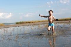 Boy running in healing mud. Boy is running in healing mud, Russia Stock Images