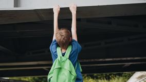 Boy with a running jump and hangs on a metal structure. Cool footage. Sports boy stock video