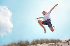 Boy running and jumping over sand dune on beach vacation stock photo
