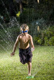 Boy running through lawn sprinkler Stock Image