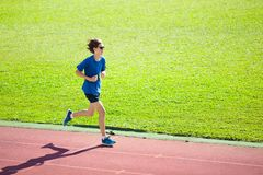 Teenager boy running on race track. Kids run. stock image