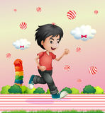A boy running outside with candy balls Stock Photo