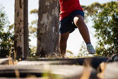 Boy running over tyres during obstacle course training Royalty Free Stock Photography
