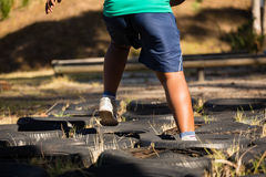 Boy running over tyres during obstacle course training Royalty Free Stock Images