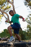 Boy running over tyres during obstacle course training Royalty Free Stock Image