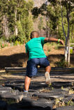 Boy running over tyres during obstacle course training Stock Photo