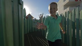 Boy running in playground maze. Active and cheerful boy running through the labyrinth on outdoor playground. Fun and leisure for children stock video footage
