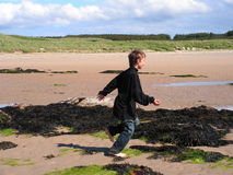 Boy Running and Playing. A pre teen boy running and playing on the beach and through the rockpools barefoot Royalty Free Stock Photos