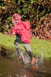 Boy Running Through A Puddle Royalty Free Stock Image