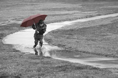 Boy running in the rain. A young boy enjoys a rainy day by stomping in a puddle Stock Image