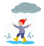 Boy running in the rain puddles Stock Photos