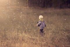 Boy running through raindrops in field