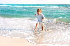 Boy running in the sea Stock Photo