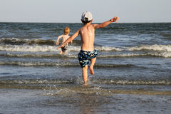 Boy running into the sea Stock Photos