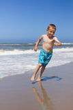 Boy running and smiling at beach Stock Photography