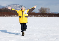 Boy running on snow in park Royalty Free Stock Image