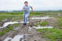 Boy, running, sports, exercise, fat, baby weight, lose weight, active, heavy Royalty Free Stock Photo