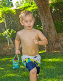 Boy Running in the Sprinklers. A cute young boy running through the water from a sprinkler Stock Image