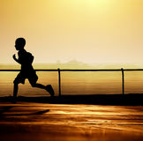 Boy running at sunset Stock Photography