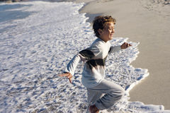 Boy (8-10) running in surf, smiling, side view, sea lapping on sandy beach Royalty Free Stock Photography