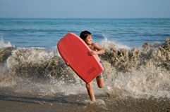 Boy running with surfing board Royalty Free Stock Photo