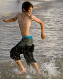 Boy Running with Tide. Young boy running towards shore from incoming tide Royalty Free Stock Photography