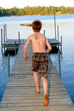 Boy running to the lake Royalty Free Stock Photos