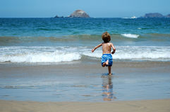 Boy running to the sea Stock Images