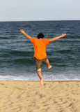 Boy running to the sea Stock Photos