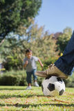 Boy running towards the football Stock Images