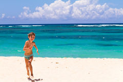 Boy running on a tropical beach. With turquoise water Royalty Free Stock Photo