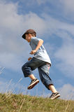 A boy running up a grass hill. A boy running up a hill stock photo