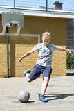 Kicking a ball in a street soccer pitch stock photo