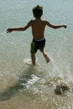 Boy running into the water. Young boy running into the ocean with a splash stock image