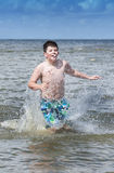 Boy running in water splash Royalty Free Stock Images