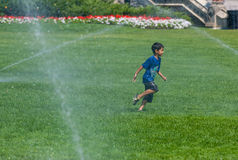 Boy Running among Water Sprinklers Royalty Free Stock Photo