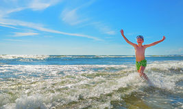 Boy running through the water Royalty Free Stock Photo