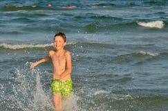 Boy running through the waves Stock Image